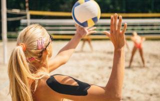 Frau mit Tapes beim Beachvolleyball